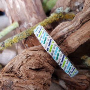 Bracelet tissage bleu vert gris sur fond blanc monté sur jonc acier