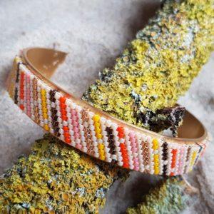 Bracelet tissage multicolore tons orangés fond blanc cassé monté sur jonc acier doré